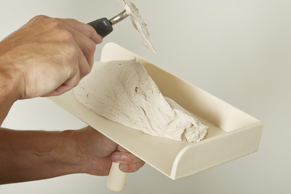 Schep met de troffel een paar moppen stucmortel op het raapbord.